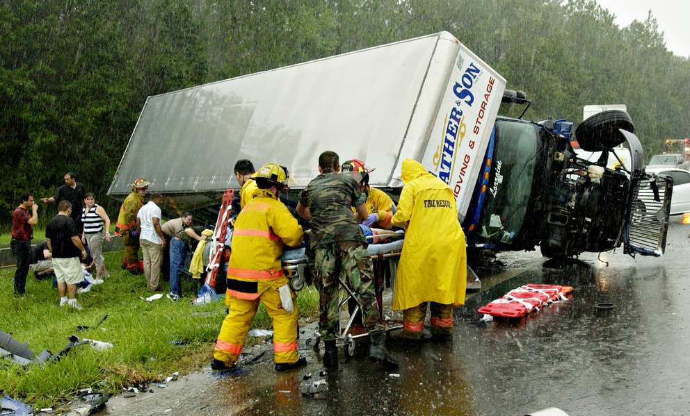 A moving and storage van lays on top of a station wagon in the East bound lane of State Road 528 in East Orange County, Fla., after crashing on a road slick from heavy rain from the outer bands of Hurricane Charley, Friday, Aug. 13, 2004. The East bound lane of SR 528 was closed for hours. Orange County Fire Rescue used the Jaws of Life to free the victems from the car. (AP Photo/Florida Today, Craig Rubadoux)