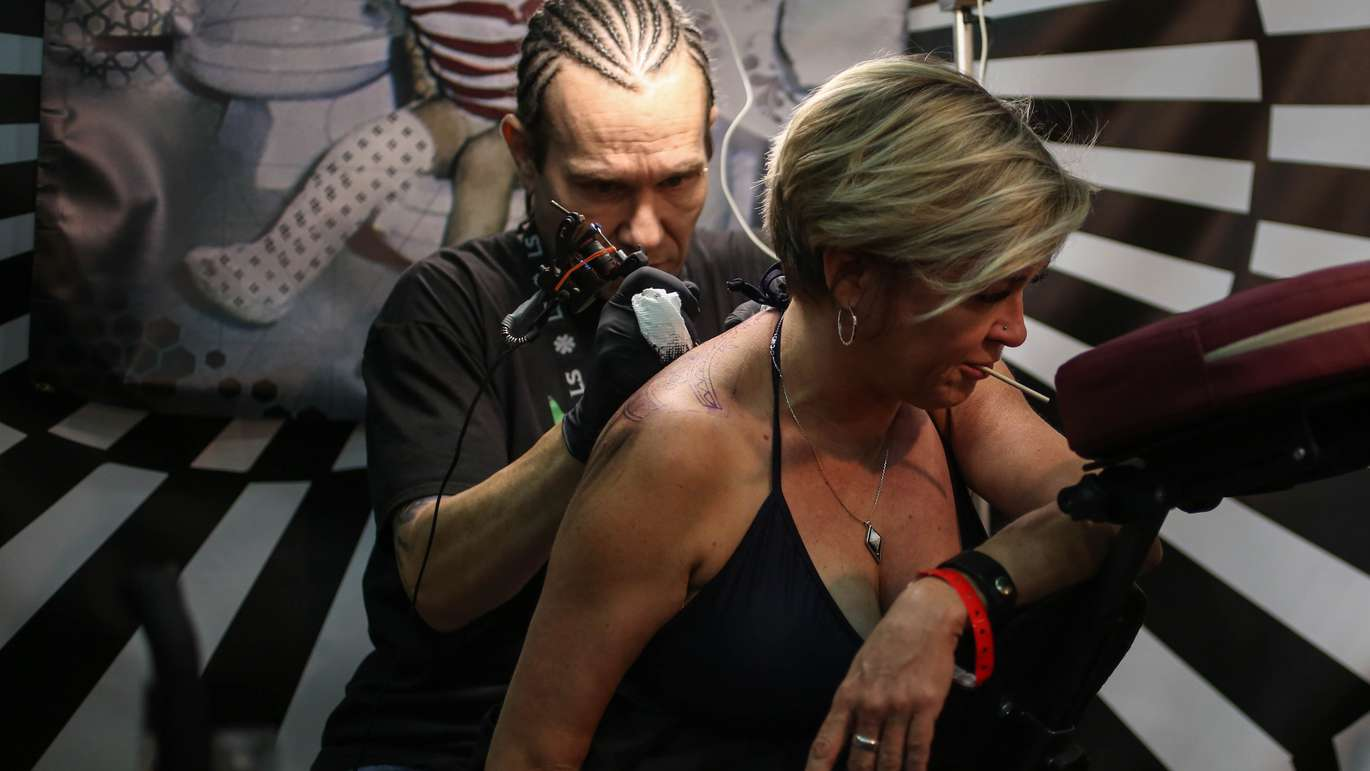 Becky Gregory gets a full back tattoo by artist Greg Koske, 44, from St. Petersburg, at the annual, Ink Mania Expo taking place in the Coliseum, St. Petersburg. MARTHA ASENCIO RHINE   Times