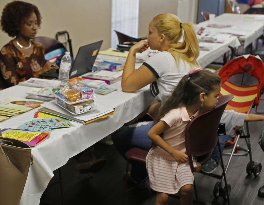 Puerto Rican evacuee Ivana Reyes, 22, talks with Ayleen Correa with the Florida Department of Health, while her daughter Shamira Melendez, 4, shares her chair at a clinic for evacuees at the Hispanic Outreach Center on Nov. 2, 2017. (JIM DAMASKE | Times)
