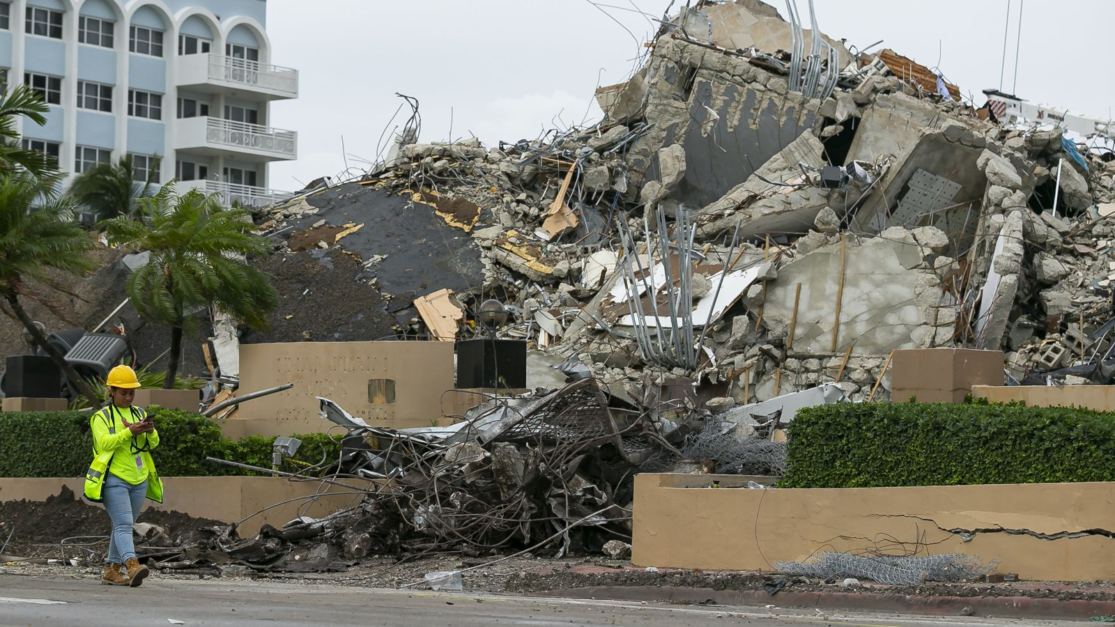 A worker makes her way past the rubble and debris of the Champlain Towers South condo in Surfside, Fla. on Tuesday, July 6, 2021.  (Matias J. Ocner/Miami Herald via AP)