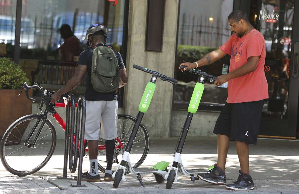 A man parks his rented dockless scooter outside of a restaurant in Atlanta. Cities across the U.S. are grappling with how to deal with electric scooters that have begun appearing in sidewalks overnight without any regulations. (AP Photo/Brinley Hineman, File)