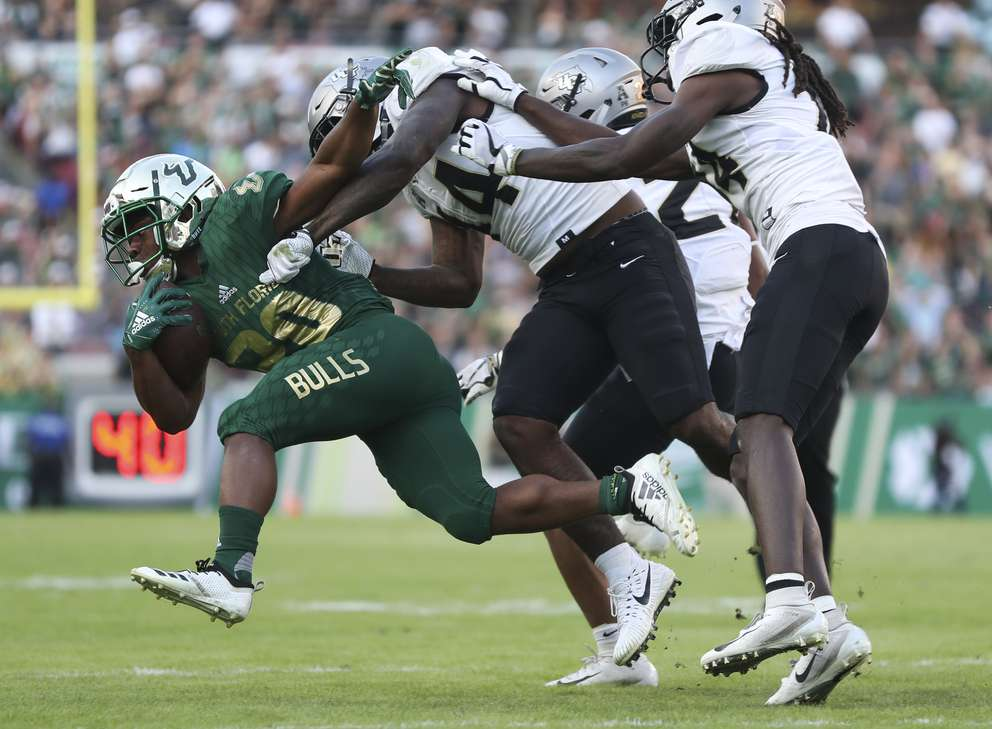 USF running back Johnny Ford (20) tries to escape a tackle during the first quarter. [MONICA HERNDON | Times]