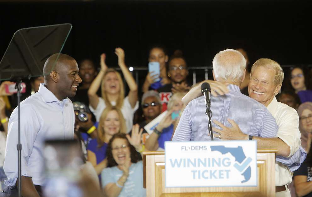 OCTAVIO JONES | TimesFormer Vice-President Joe Biden, center, hugs U.S. Sen. Bill Nelson while Florida Gubernatorial Democratic candidate Andrew Gillum looks on during the Florida Democratic Party rally held at the University of South Florida in Tampa, Florida on Monday, October 22, 2018.