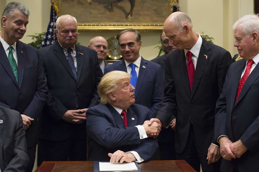 President Donald Trump shakes hands with Florida Gov. Rick Scott after signing S. 544 the Veterans Choice Program Extension and Improvement Act in the Roosevelt Room at the White House in Washington, D.C., on April 19, 2017. (Molly Riley / Pool via CNP)