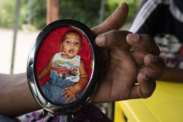 """Carlos Martínez, de 27 años, de Caracas, Venezuela, sostiene una foto enmarcada de su hijo, que lleva en su mochila como recordatorio de por qué está haciendo todo. """"Él es la razón por la que me arriesgo"""", dijo Martínez. Había cruzado la frontera desde Venezuela hacia Cúcuta, Colombia, el sábado 7 de diciembre de 2019  ."""