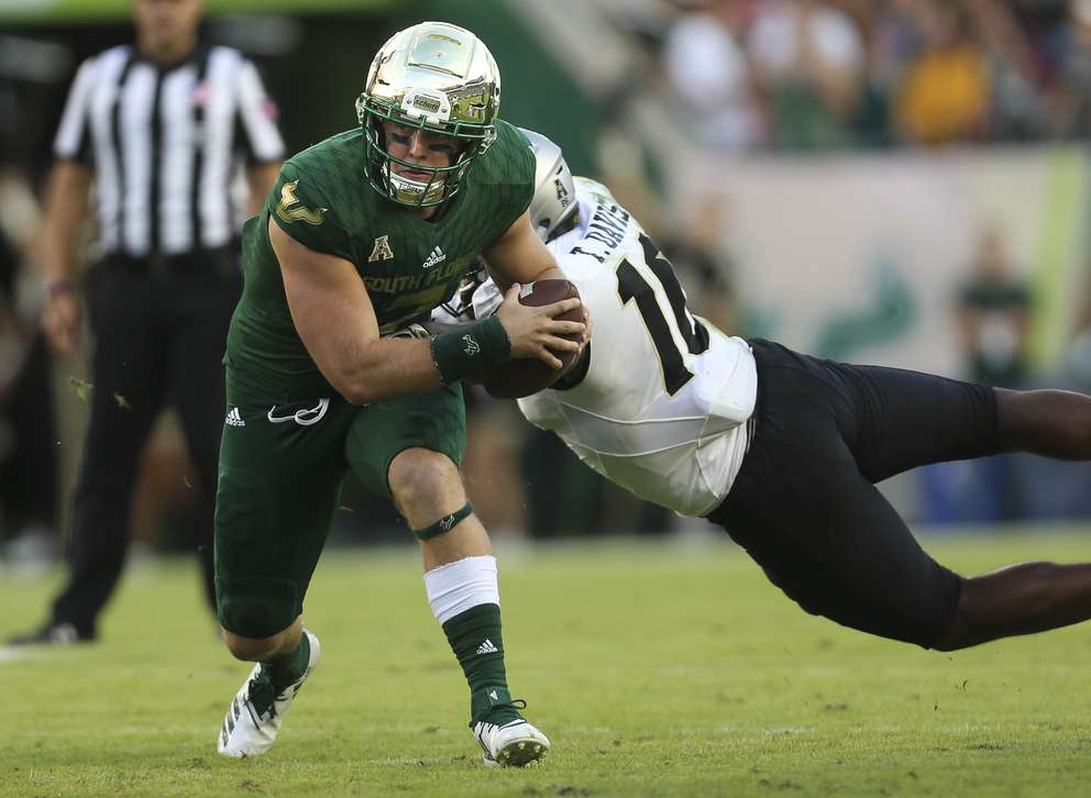 USF quarterback Brett Kean (7) gets stopped by UCF Knights defensive lineman Titus Davis (10) during the second quarter. [MONICA HERNDON | Times]