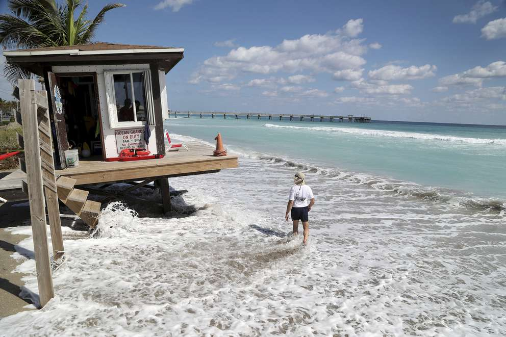 Waves pound a Dania Beach lifeguard station Tuesday as high tide approaches. The Dania Beach parking lot which includes access to a marina, the Dania Beach Bar &Grill and the Quarterdeck restaurant have been closed for three days. The parking lot is experiencing flooding and sand buildup. (Susan Stocker/South Florida Sun-Sentinel via AP)