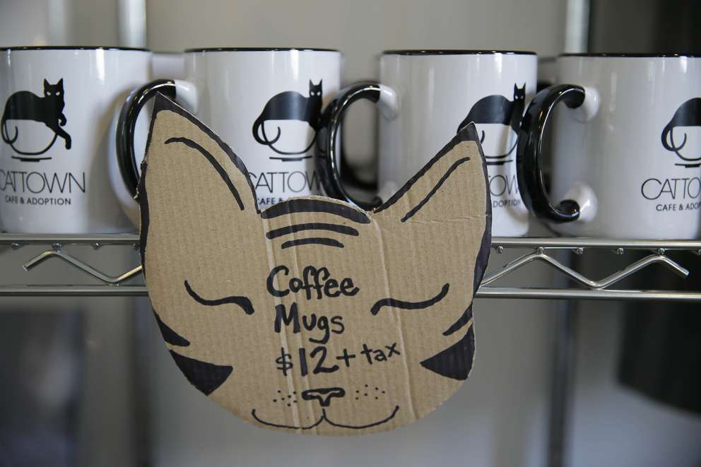In this photo taken Thursday, Nov. 6, 2014, coffee mugs are shown for sale at a cat cafe in California. Customers pay to pet cute kitties while sipping on tea or expresso drinks. [Eric Risberg | AP]