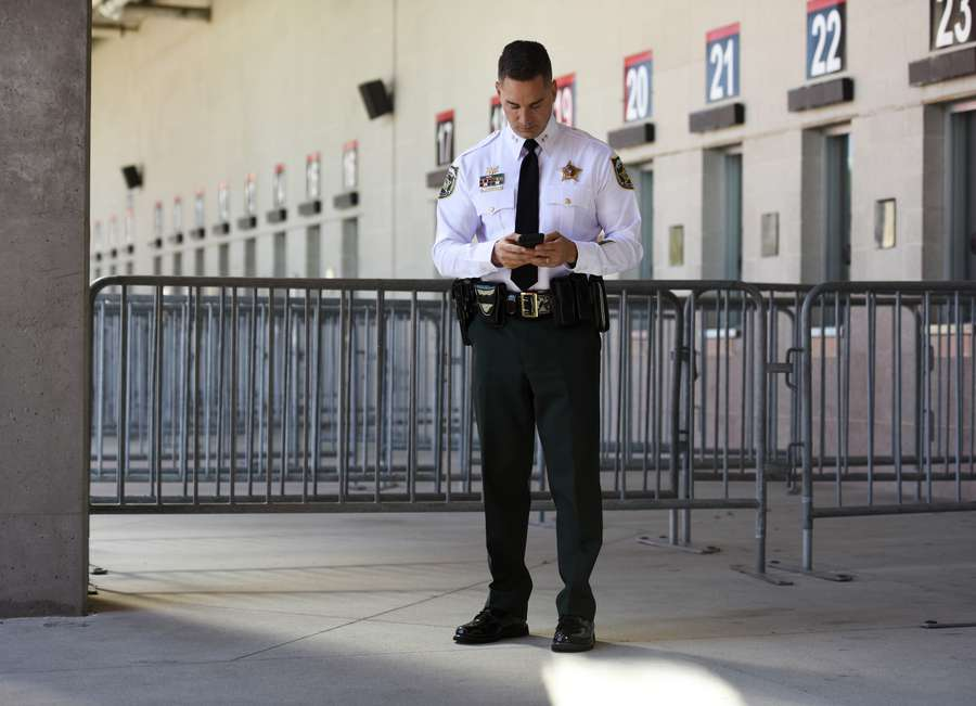 "Sheriff Chad Chronister stays connected by phone during a security meeting in April at Raymond James Stadium. Chronister said he gets invited to a lot of events and tries not to say no. He sees introducing himself and using social media to share what he's doing as a ""vital part"" of his job. [CHRIS URSO 