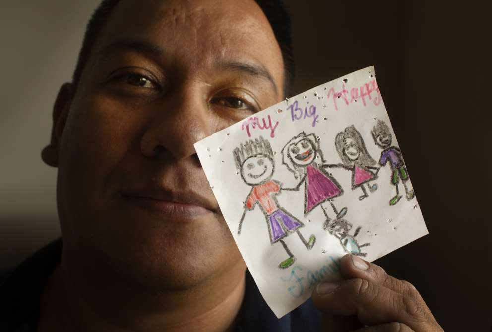 Victor Becerra holds a picture drawn by his son. Victor has been a single parent to three kids while his wife has been stuck in Mexico. JOHN PENDYGRAFT | Times