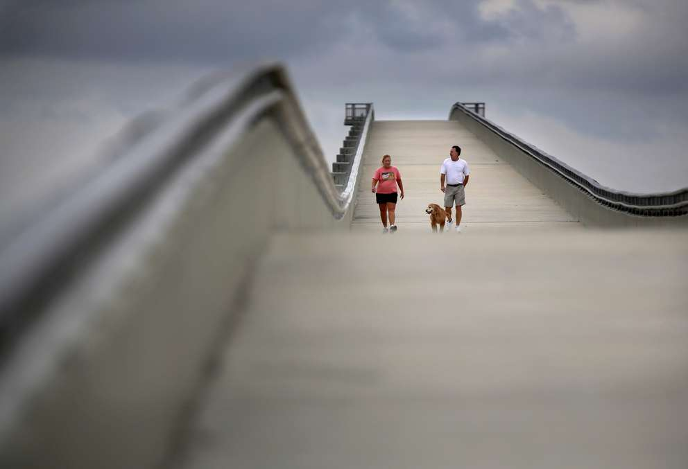 Dawn White, left, and Dennis White, of Clearwater, take one of their twice-weekly walks across the Courtney Campbell Trail bridge on Wednesday with their golden retriever Roxy in Tampa. DOUGLAS R. CLIFFORD I Times (2015)