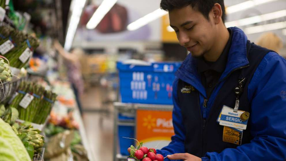 A Walmart personal shopper picks out produce to fulfill pick-up and delivery orders. [Courtesy of Walmart]