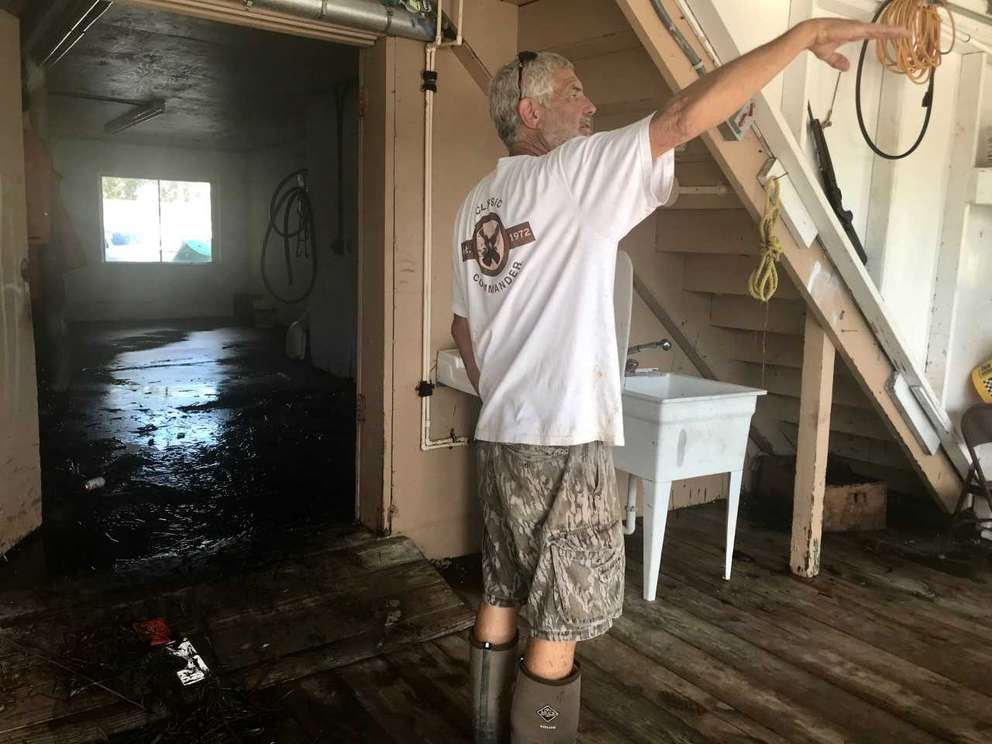 Rick Tooke of St. Marks holds up his hand to indicate where the water line was during the storm surge at his crabbing shop, which is right along the St. Marks River leading to the Gulf.