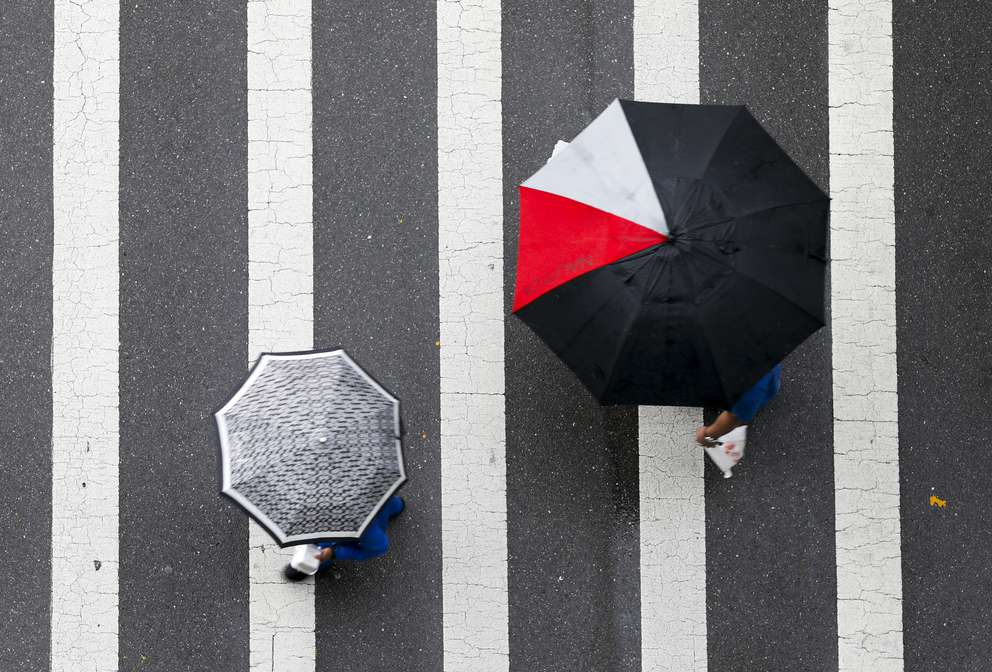 Unidentified pedestrians cross Whiting Street at the intersection of Franklin Street while carrying umbrellas Wednesday, May 30, 2018 in Tampa. [Chris Urso | Times]