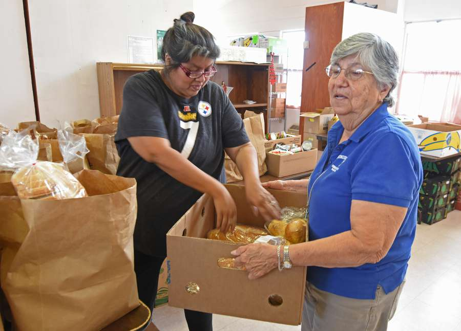Margarita Romo (right), with volunteer, Rosalinda Campanilla (left) and other volunteers with the Farmworkers Self-Help organization package and hand out groceries to needy families at the Norma Godinez Learning Center in Dade City on Thursday, May 24, 2018. Times | LANCE ROTHSTEIN