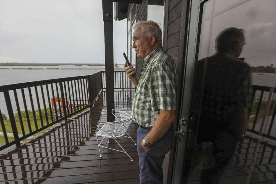 Albert Yates, 79, takes a phone call as he stands on the balcony of his home along Sanddollar Point Wednesday, Oct. 10, 2018 in Ozello. The low lying area has been prone to flooding in the past and most residents have already evacuated. Yates, a retired builder imported Brazilian walnut -- Òiron wood,Ó he said, so hard you canÕt nail into it, only drill. From it he constructed his 13.5-foot high, Category 4 hurricane-rated home, with pylons that go five feet into bedrock.