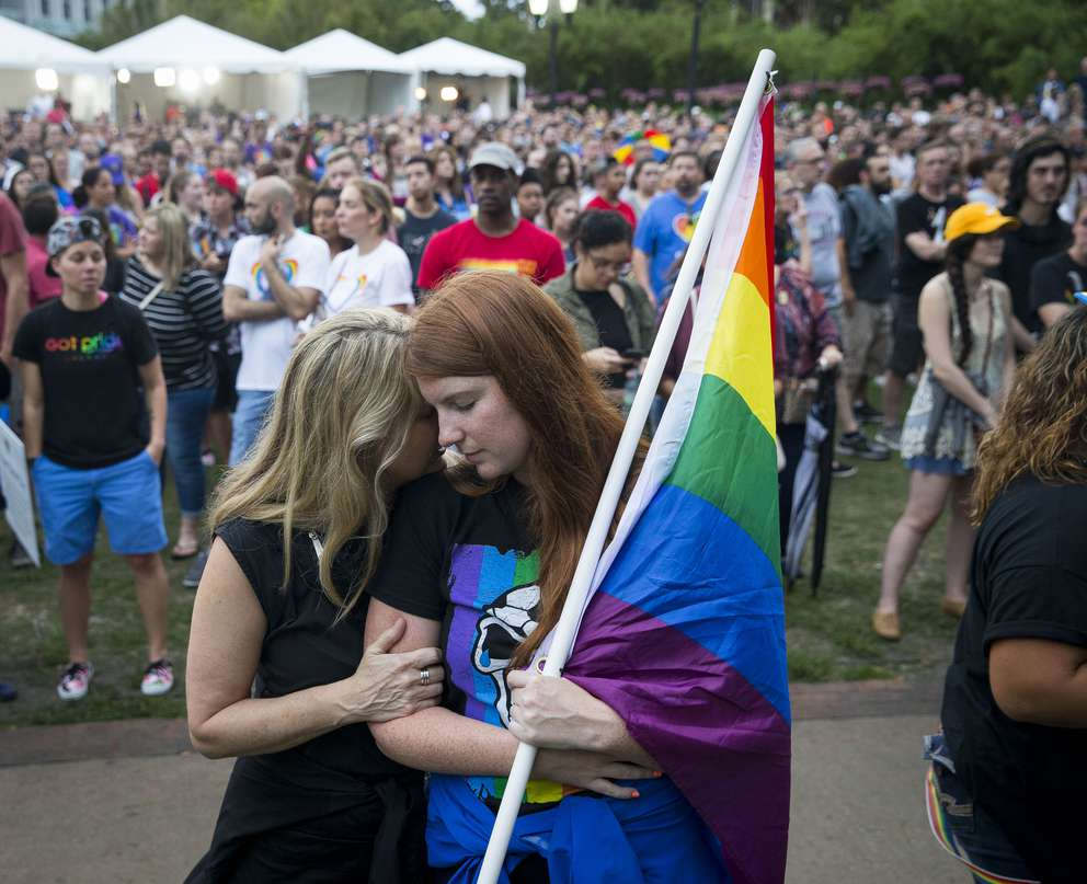 LOREN ELLIOTT | Times McKenna Post holds a rainbow flag as her mother, Randa Black, hugs her during a vigil at Lake Eola honoring the 49 lives lost exactly one year earlier in a mass shooting inside Pulse, a gay nightclub, in Orlando, Fla., on Monday, June 12, 2017. The event was part of