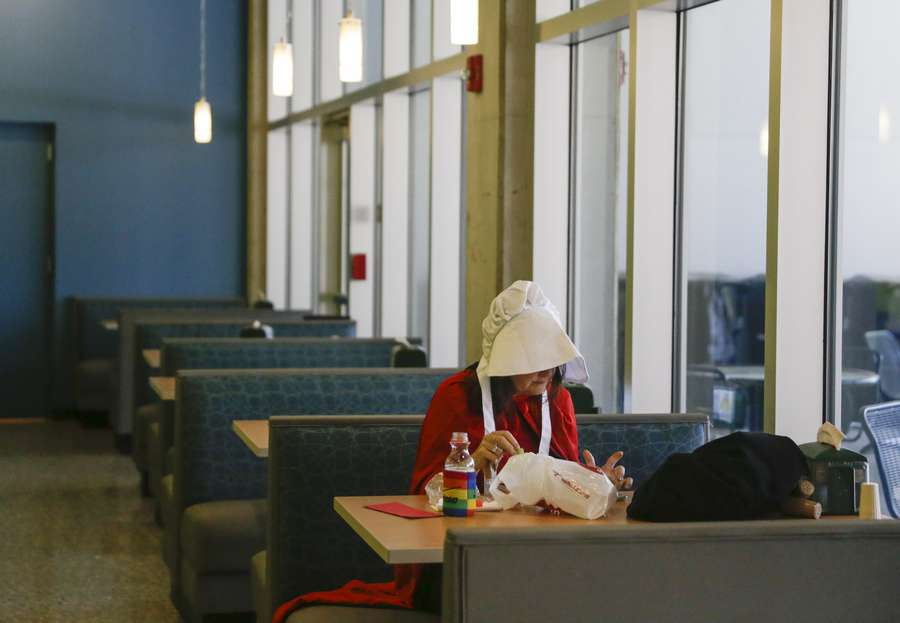 """Farah Stokes, of Tampa, dressed as a Handmaid from the show """" The Handmaid's Tale,"""" takes a lunch break during the Road to the Ballot Public Hearing Tour at University of South Florida St. Petersburg's Student Center on Tuesday in St. Petersburg. Stokes, a member of Florida's League of Woman Voters, came to oppose Proposal 22, which she believes is an intrusion to women's reproductive rights. (GABRIELLA ANGOTTI-JONES 