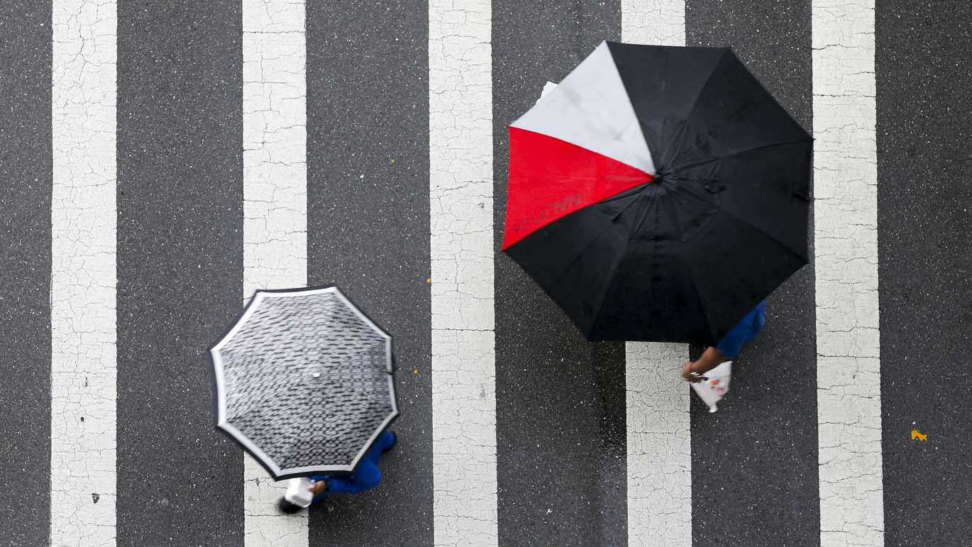 CHRIS URSO   Times Unidentified pedestrians cross Whiting Street at the intersection of Franklin Street while carrying umbrellas Wednesday, May 30, 2018 in Tampa. Rain continued to fall on the Tampa Bay region Wednesday. Rain chances will stay near 60 percent with afternoon highs in the lower 80s, forecasters said.