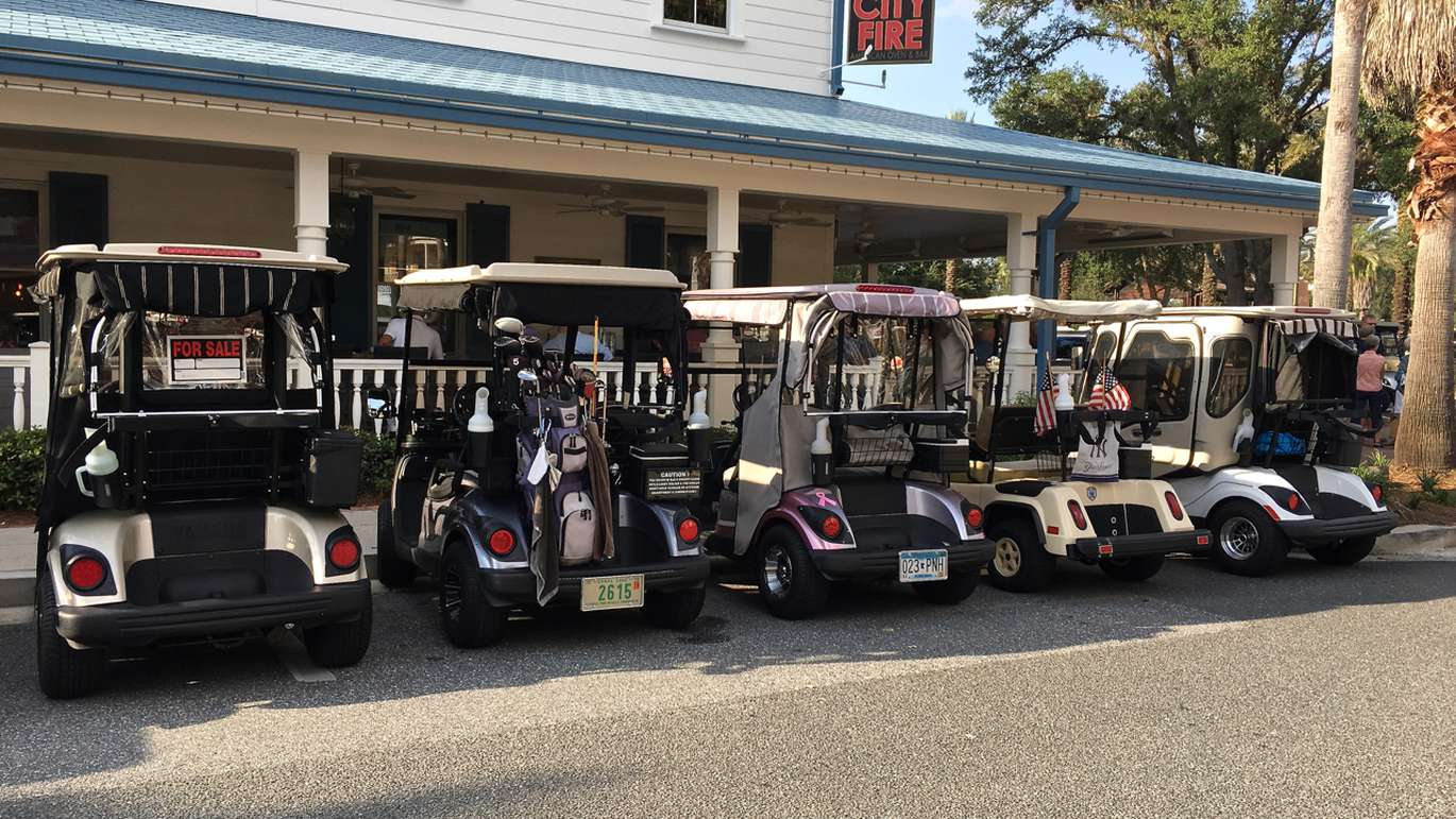 Golf carts lined up outside a bar during happy hour at The Villages. (Alex Leary | Times)