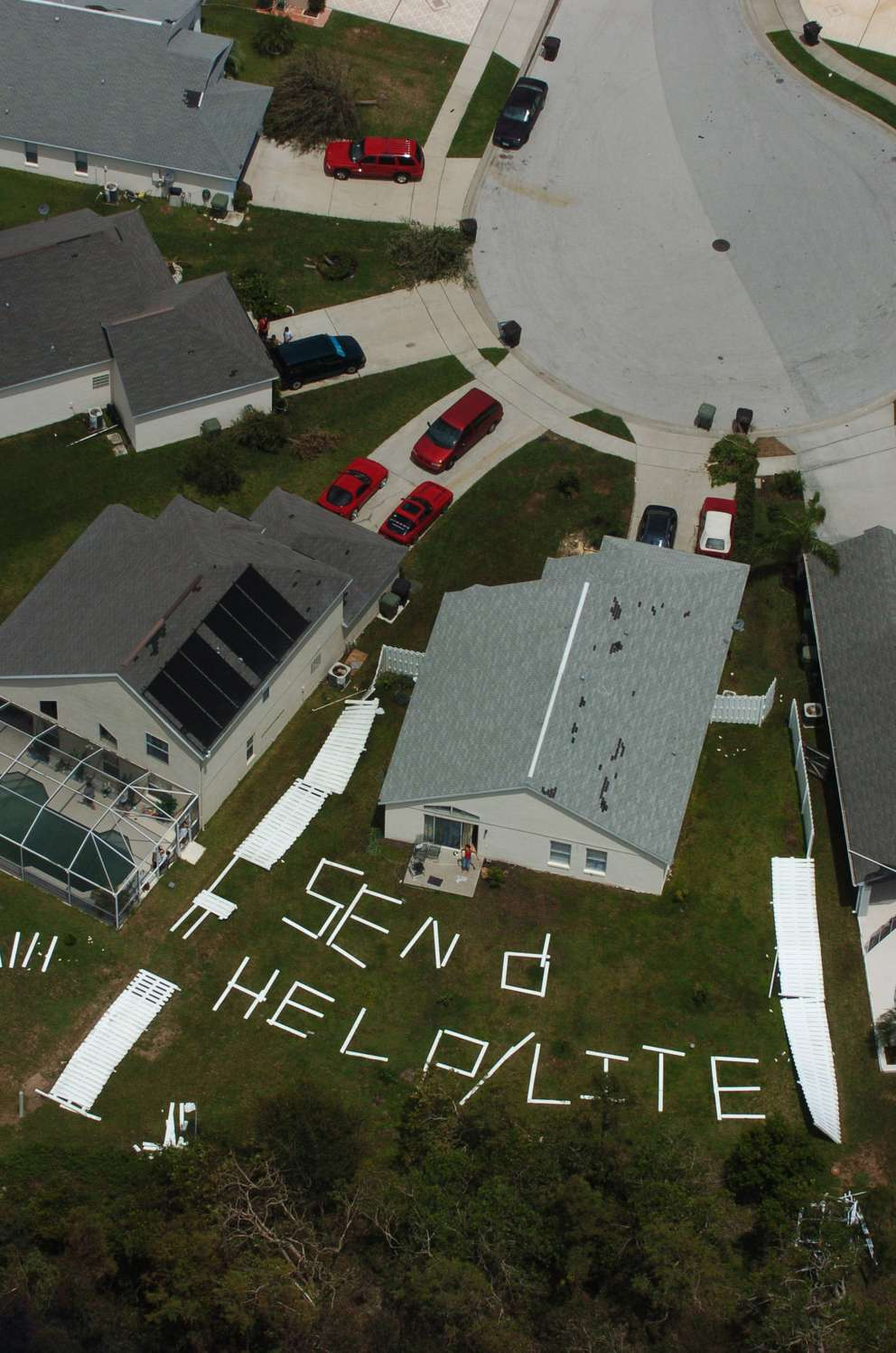 A request for help is shown in the backyard of a home in Osceola County, Fla., Thursday, Aug. 19, 2004. People living in the subdivision on Thursday were among the thousands of customers still without power following last week's storm. (AP Photo/Orlando Sentinel, Red Huber)