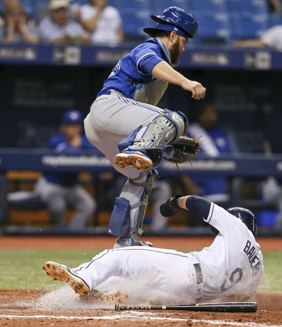 Tampa Bay Rays first baseman Jake Bauers (9) slides underneath Toronto Blue Jays catcher Russell Martin (55) during the seventh inning Monday, June 11, 2018 in St. Petersburg. Both Tampa Bay Rays first baseman Jake Bauers (9) and Tampa Bay Rays catcher Wilson Ramos (40) scored on a fielder's choice hit by Tampa Bay Rays second baseman Joey Wendle (18). [CHRIS URSO | Times]