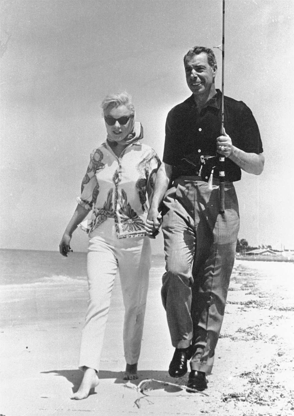 A March 1961 photo shows actress Marilyn Monroe and ex-husband, former New York Yankee ball player Joe DiMaggio, happily walk the shores of the Gulf of Mexico as they enjoy a day together at Bellaire, Florida. [AP]