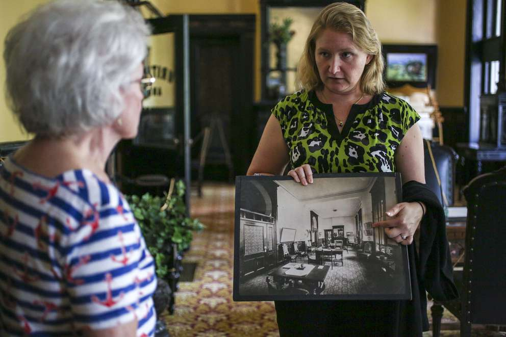 Lindsay Huban shows Stephanie Carlos, 75, a vintage photograph detailing the room they're in at the Henry B. Plant Museum at Tampa University. MARTHA ASENCIO-RHINE | Times