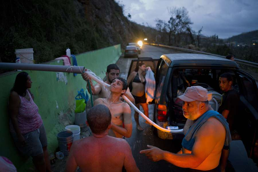 People affected by Hurricane Maria bathe in and collect water piped from a creek in the mountains in Naranjito, Puerto Rico, on Thursday, Sept. 28, 2017. Residents of the area drive to the pipes to bathe because they were left without water supplies by the damage caused by Hurricane Maria. The pipe was set up by a neighbor who ran it from a creek in his property to the side of the road in order to help those left without water. [Ramon Espinosa | Associated Press]