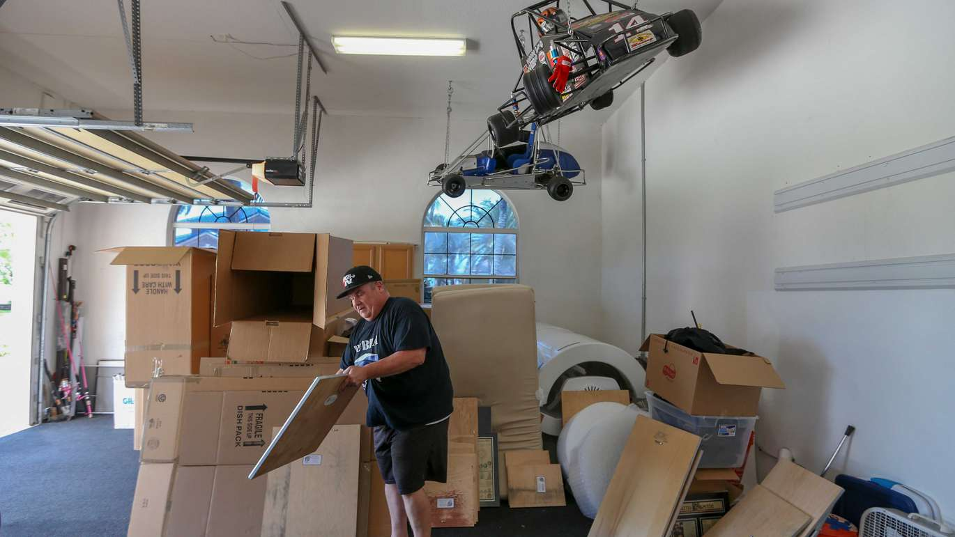 Bubba in his garage with boxes of framed news stories from his career. [CHRIS URSO   Times]