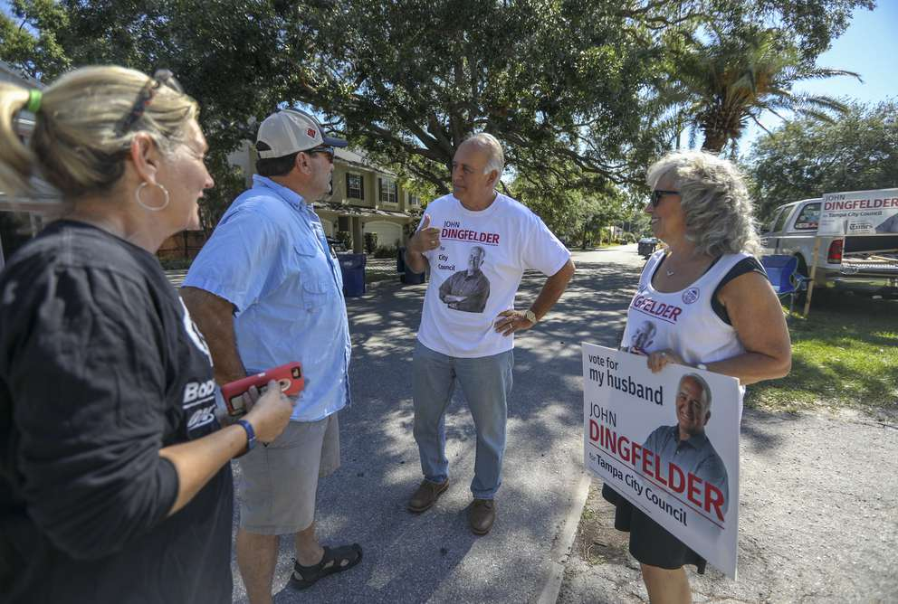 Tampa City Douncil District 3 candidate John Dingfelder, second from right, speaks with James Catalano, 58, second from left, and his wife Gaylon, 57, of Tampa as the candidate's wife Lynn Marvin Dingfelder, right, looks on outside Covenant Life Church on Tuesday. [CHRIS URSO | Times]