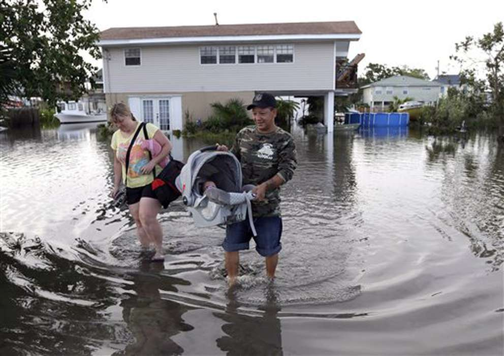 Tony Rodriguez, right, carries his baby daughter Nicole as they and his wife, Jodi Clelland, leave their flooded home in the aftermath of Hurricane Isaac in Slidell, La., on Aug. 31, 2012. [Associated Press]