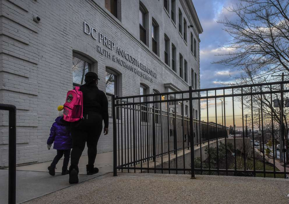 A parent escorts her child to DC Prep, an elementary school in Washington, D.C., where students and staff have been unnerved by recent nearby gunfire. [Washington Post photo by Bill O'Leary]