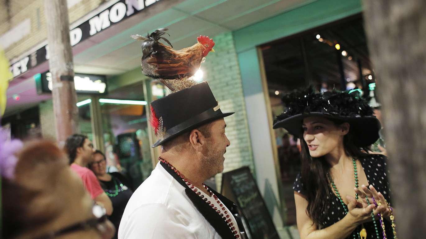 Charlie Livingston, left, talks with Meggie Castro right outside of the Bad Monkey bar in the Ybor City neighborhood in Tampa on Tuesday, February 13, 2018. Ybor's annual James E. Rooster Parade celebrates the Latin District's chicken heritage. It has long been said that the chickens in Ybor were brought there by the immigrants and have endured ever since. Some longtime residents of Ybor say this is only partially true. [OCTAVIO JONES   Times ]
