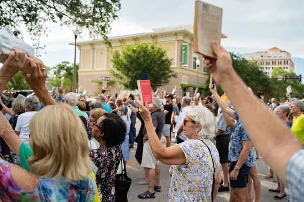 Demonstrators raise books during the Unite Against Hate vigil outside the Florida Holocaust Museum Thursday in St. Petersburg. The group gathered Thursday in response to the recent vandalism.