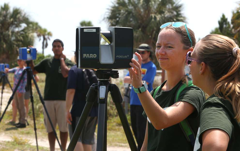 University of South Florida graduate students Kiana Sladicki, center, and Cassie McCabe, right, crank up a 3D scanner at the Egmont Key lighthouse. They're part of a team producing detailed images of historic sites on the island before the sites are lost to erosion. [SCOTT KEELER | Times]