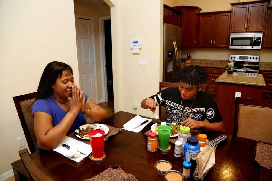 Tameka Baldwin shares a homemade stew with her son, Rafael Oriano. Baldwin's grandmother gave her the land where the home sits. [DOUGLAS R. CLIFFORD/Times]