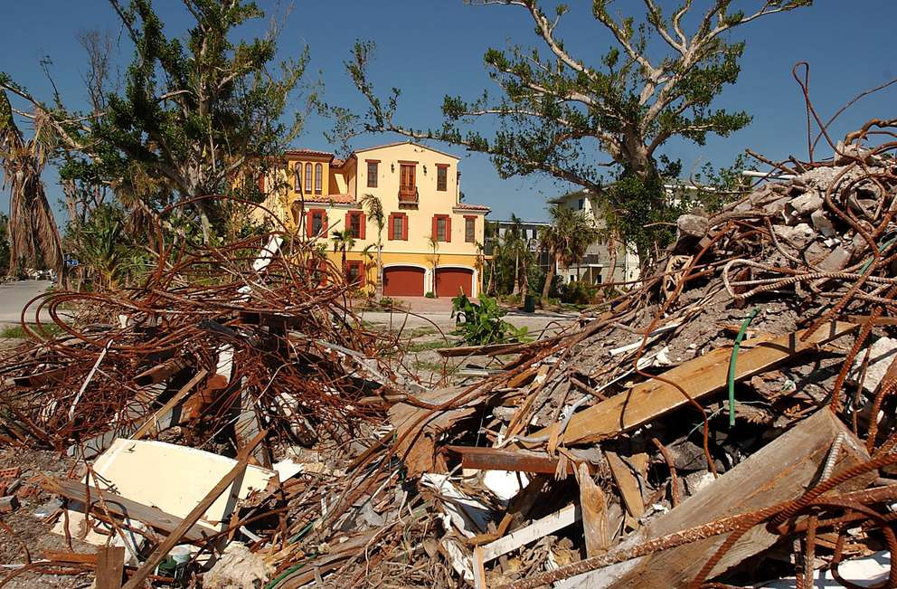 An upscale home on Capitiva Island is framed by mounds of debris from a damaged home near Captiva Drive. The island was hit hard by Hurricane Charley's high winds. Many of the expensive homes can now be seen from the road since the island's vegetation was blown down by Charley's winds. Times (2004)