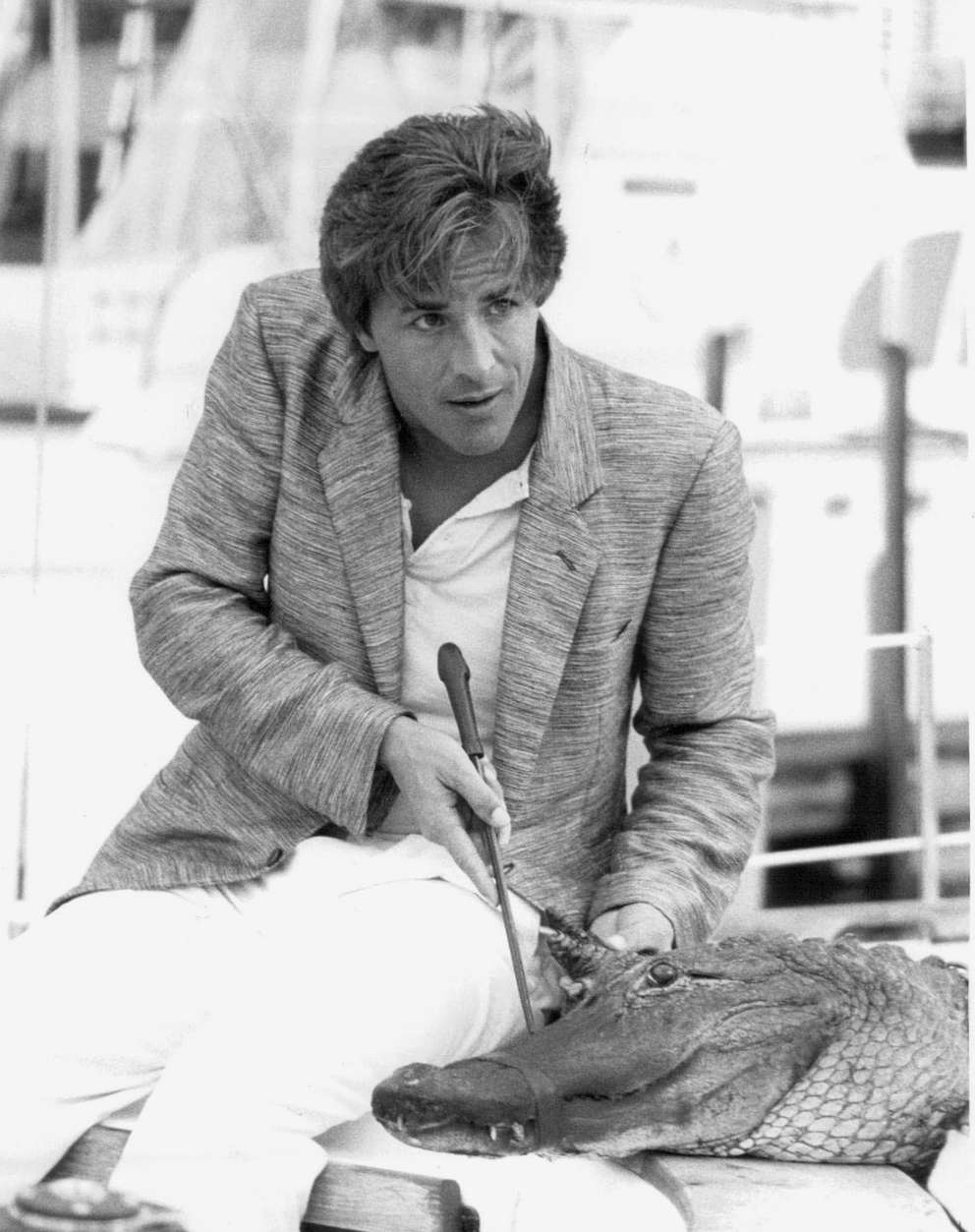 Detective Crockett (played by Don Johnson) carefully puts the clamps on Elvis, his pet alligator, before continuing his undercover assignment on NBC-TV's Miami Vice in 1985. [Times archives]