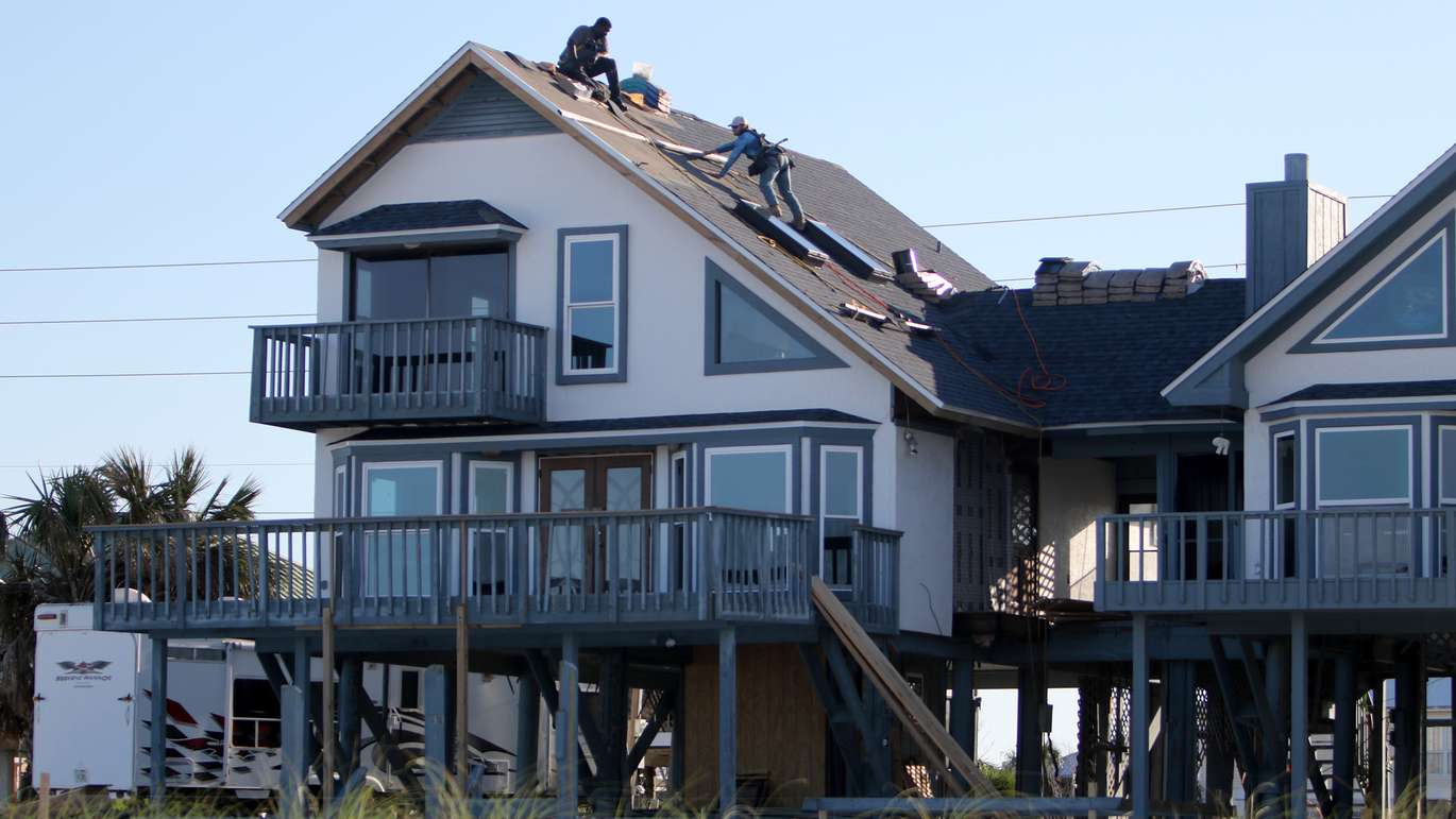 Roofers install shingles on a stilt home on Mexico Beach, seven months after Hurricane Michael made landfall, destroying many of the structures in the small coastal Florida Panhandle city. (DOUGLAS R. CLIFFORD | Times)