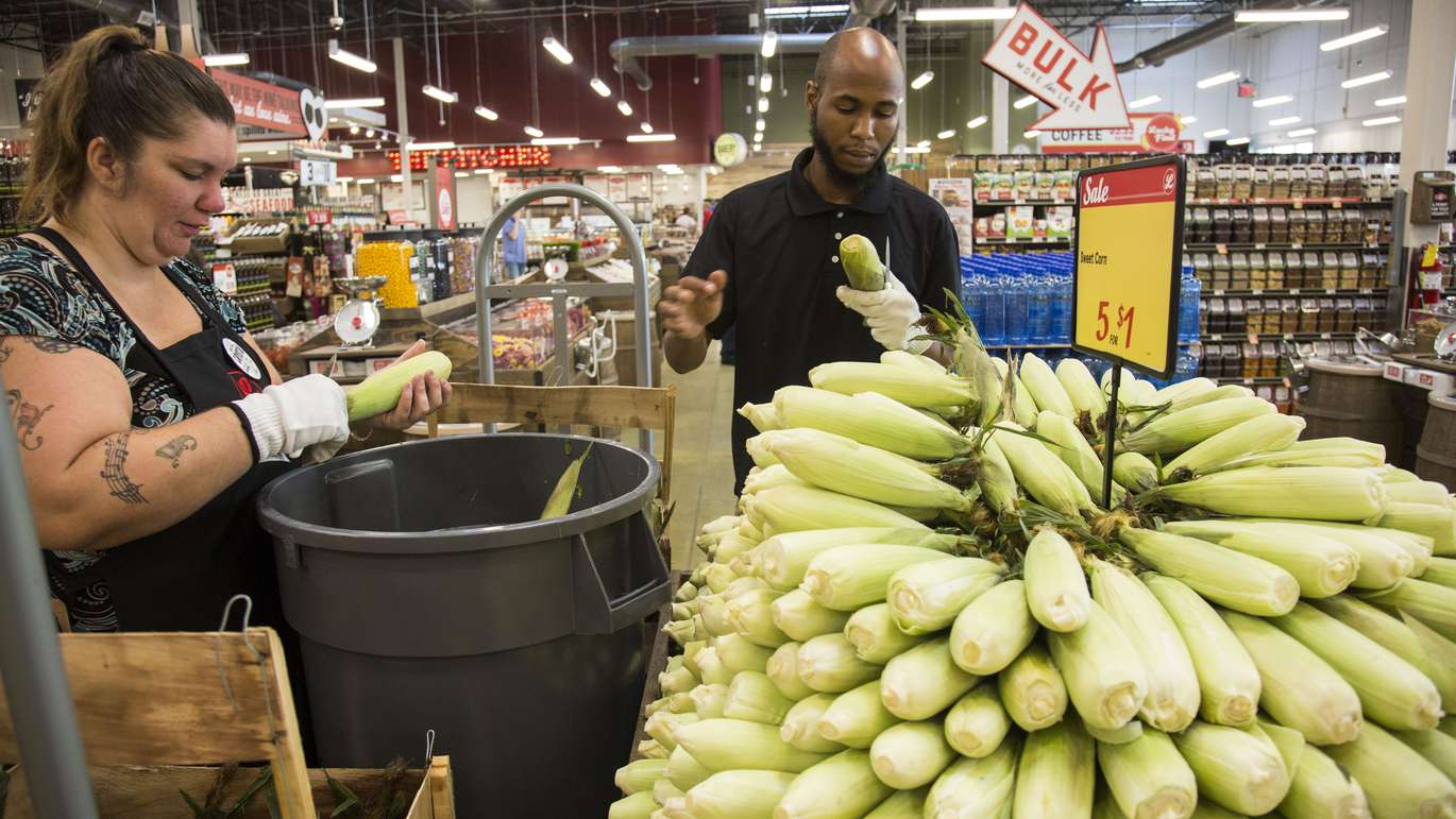 (from left to right) Produce team members Crystal Beach and J.D. Monroe trim corn to be sold at Lucky's Market in St. Petersburg on Tuesday, June 5, 2018. The Market's grand opening on June 6, 2018. [EVE EDELHEIT   Times]