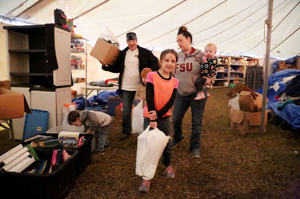 Sheila Dady, of Beacon Hill, left, gathers basic domestic supplies on Dec. 11 with Alyssa Evans, 35, of Panama City, and Evans' children, from left, Grayson Turner, 3, Tristan Gibson, 7, Faith Gibson, 8, and Amelia Downum, 1, at the city of Mexico Beach's