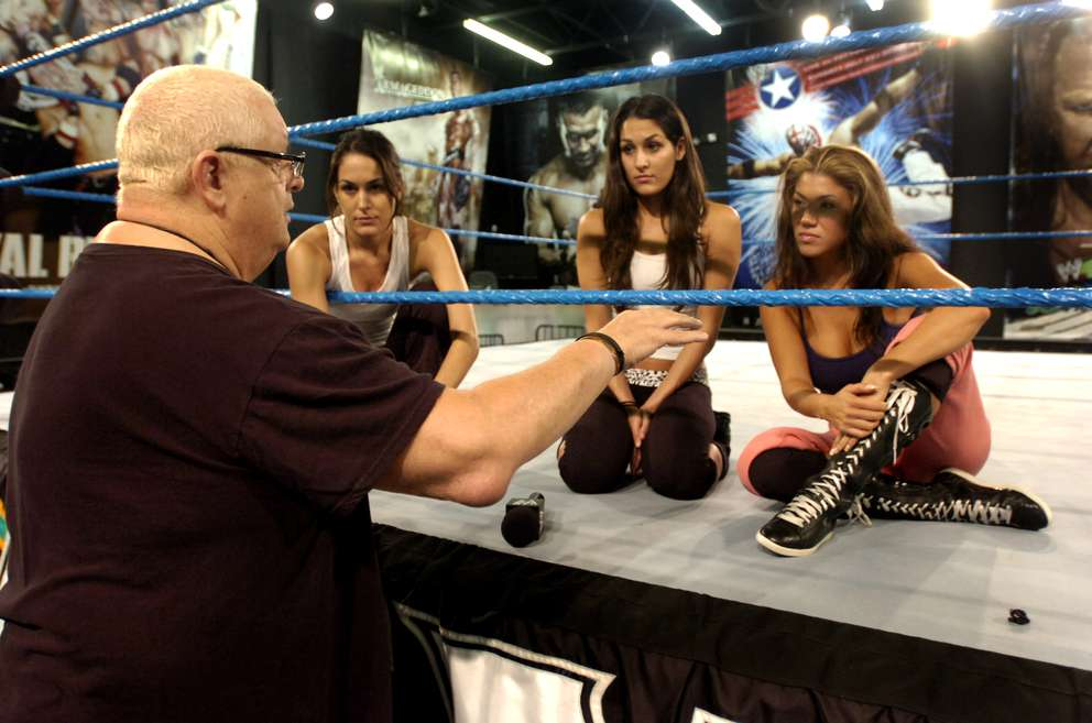 Dusty Rhodes instructs, from left, Brie and Nikki Bella, and Milena Roucka on how to interact in the ring while being filmed for television. [Times files (2008)]
