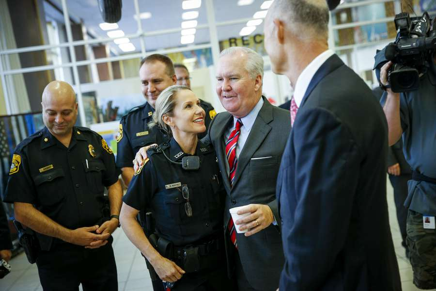 Tampa Mayor Bob Buckhorn hugs Officer Randi Whitney as he and Florida Gov. Rick Scott congratulate her on the arrest of the suspect in the Seminole Heights killings at Tampa Police Headquarters in Tampa, Fla. on Wednesday, Nov. 29, 2017. [WILL VRAGOVIC | Times]