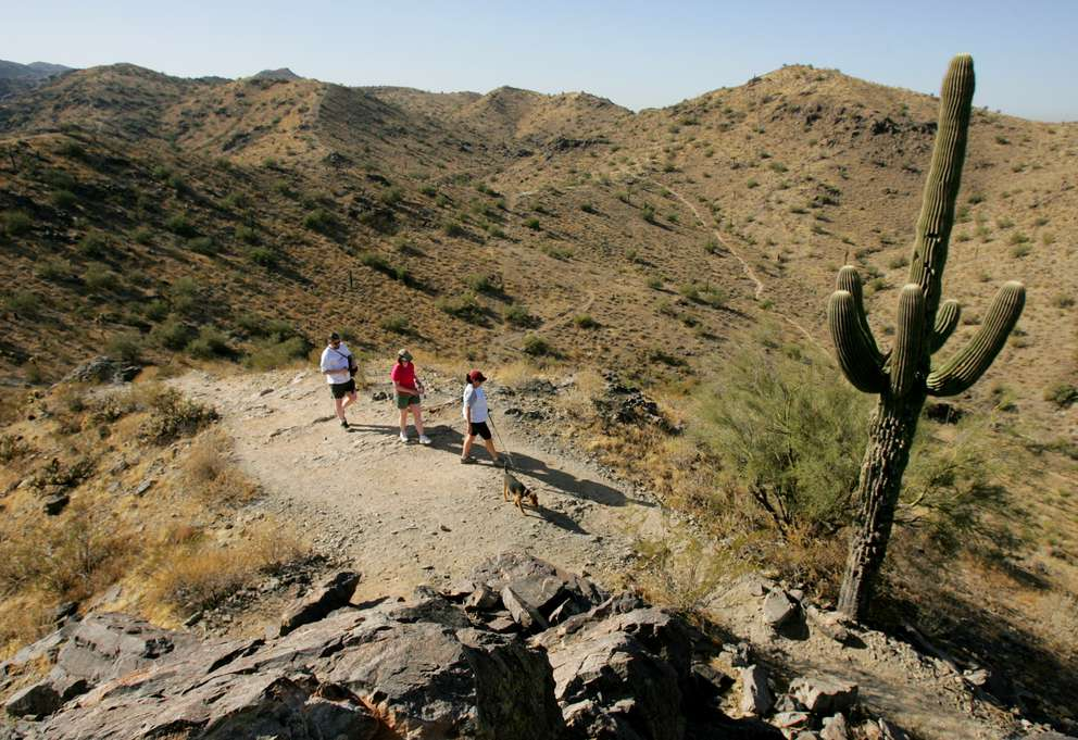 Kevin Bishop, left, and Sheila Bishop, center, of Anchorage, AK, hike with friend Erika Keenan, as she walks her dog Winston, along a hiking trail in the South Mountain Park in Phoenix. [Ross D. Franklin | AP]
