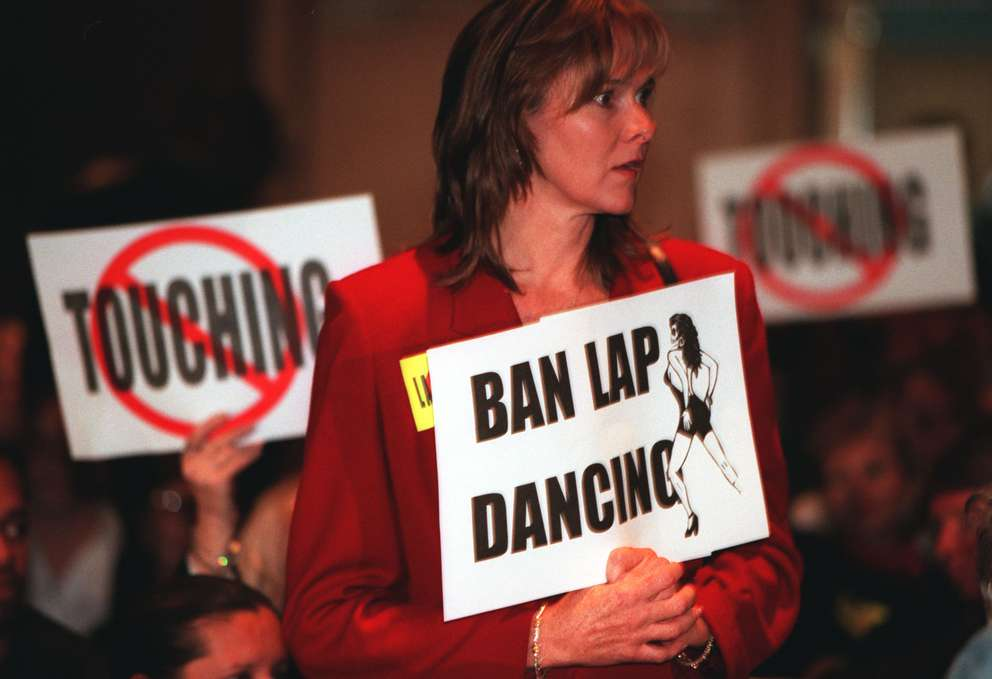 Debra Bolves holds up a sign expressing her view of lap dancing at the Tampa Convention Center. Times (1999)