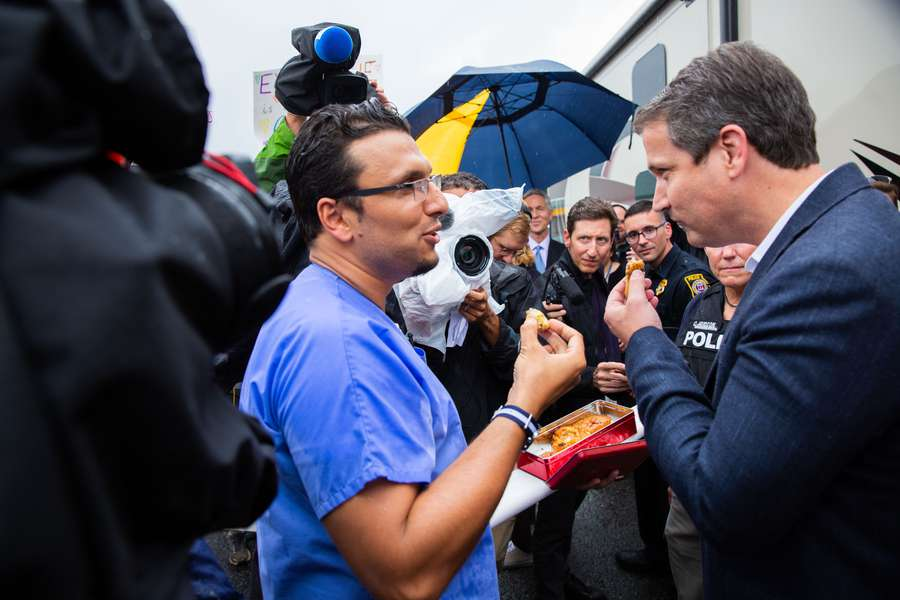 Heval Kelli shares baklava with Michael Williams at a protest of the GOP gubernatorial candidate's