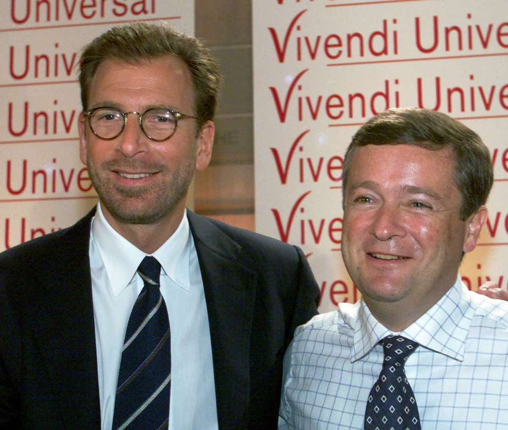 Edgar Bronfman Jr., left, president and chief executive officer of Seagram, and Jean-Marie Messier, chairman and chief executive officer of Vivendi, pose after the official announcement of their merger in 2000 in Paris. (AP Photo/Laurent Rebours)