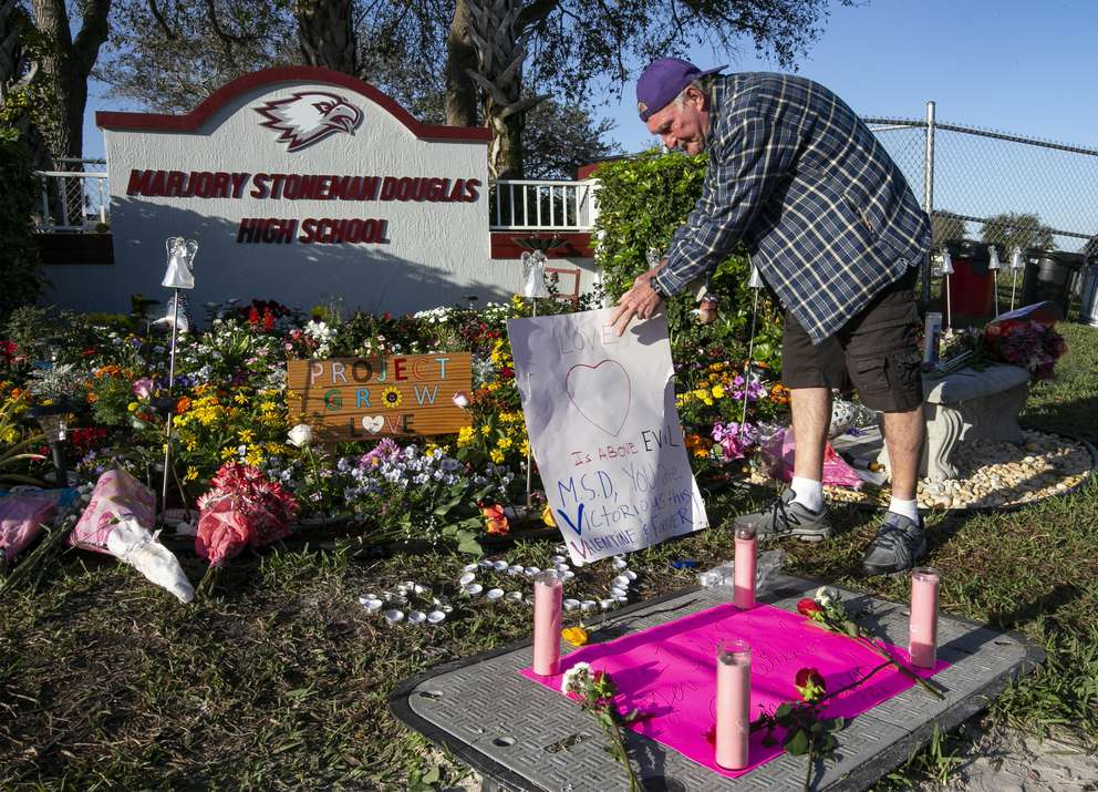Jack Jozefs places a sign at a memorial outside fthe school during one year anniversary of the shooting death of 17 at Marjory Stoneman Douglas High School in Parkland, Fl. on Thursday, Feb. 14, 2019. [Al Diaz | Miami Herald]