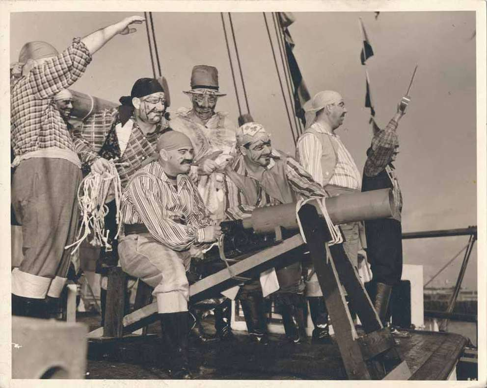 A group of pirates crowds around a cannon in 1939. [Burgert Brothers | Courtesy, Tampa-Hillsborough County Public Library System]